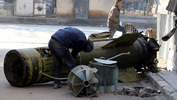 A man inspects an unexploded missile in the rebel-held besieged al-Qaterji neighbourhood of Aleppo, Syria.