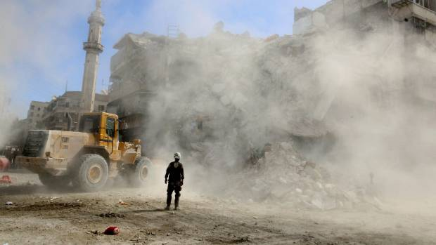 A Civil Defence member stands as a bulldozer removes debris after an air strike.