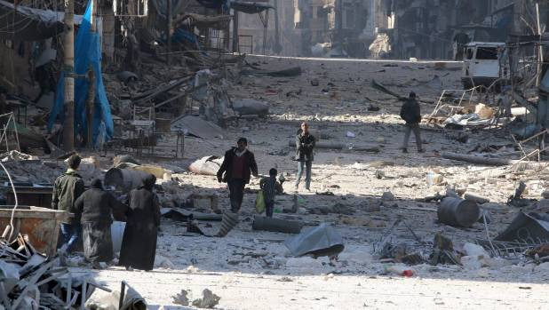 Syrians walk over rubble of damaged buildings, while carrying their belongings, as they flee clashes between government ...