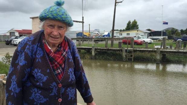 Flora Thirkettle, who's known as 'the Queen of the Kaipara', stands in front of the Helensville Cruiser Club with the ...
