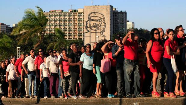 A large portrait of Cuba's late president Fidel Castro hangs from a building while people wait in line to pay their last ...