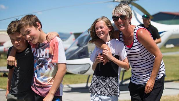 Stevie Dineen is hugged by mum Lisa Dineen after her flight with Richie McCaw. Brother Jack Dineen and cousin Reuben ...