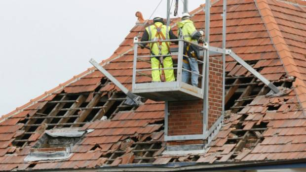 Workers removing a brick chimney and tiles from an old building at the CPIT Sullivan Campus in Christchurch.