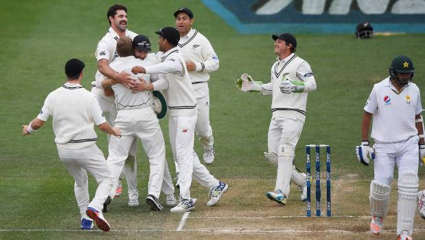 Neil Wagner is hugged by team mates as Pakistan batsman Imran Khan walks away and NZ win the series 2-0.