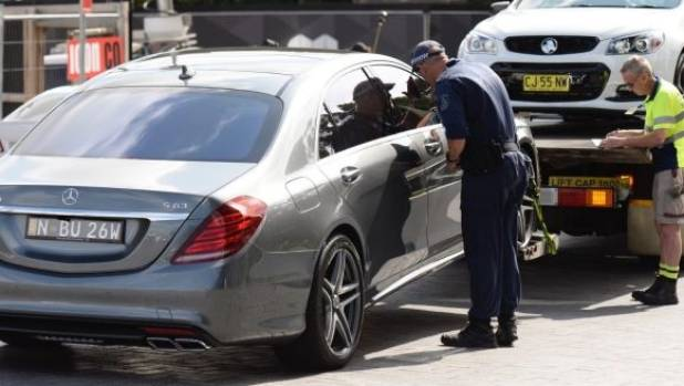 Police remove several luxury cars from an apartment building on Australia Avenue in Olympic Park.