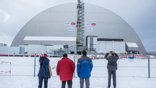 People take pictures following a ceremony to mark the movement of the New Safe Confinement sarcophagus over the ...