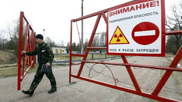 "An employee opens the gate at the checkpoint ""Maidan"" in the 30 km exclusion zone around the Chernobyl nuclear reactor."