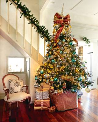 Think beyond the fairy: a big bow to top off your tree says Christmas with a flourish.