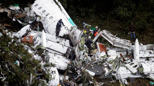 Rescuers work in the wreckage of the plane after it crashed into the Colombian jungle.
