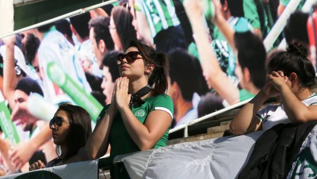 A fan of Chapecoense soccer team prays at the team's home ground.