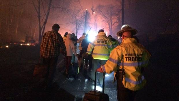 Troopers from the Tennessee Highway Patrol help residents leave an area under threat of wildfire.