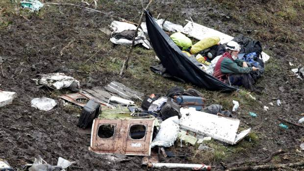 A rescue worker sits near the wreckage of a plane that crashed into the Colombian jungle with Brazilian soccer team ...