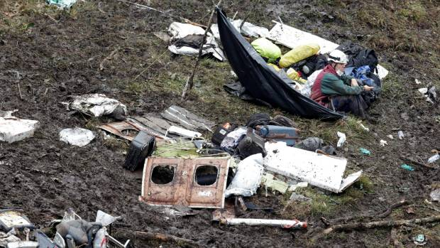 A rescue worker sits near the wreckage of the plane.