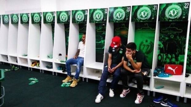 Players from Brazil's Chapecoense football club sit in the team's dressing room after learning a plane carrying their ...
