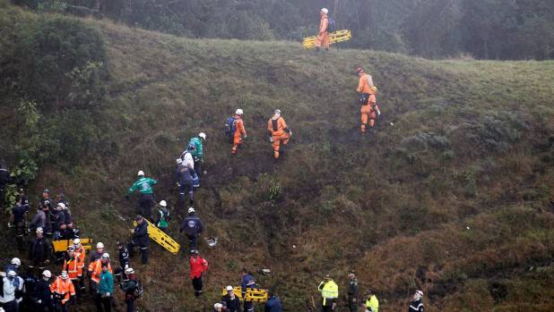 Rescuers scramble over the tough terrain as they hunt for survivors of the crash.
