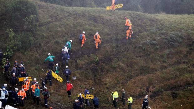 Rescue crew work near the wreckage from a plane that crashed into Colombian jungle.