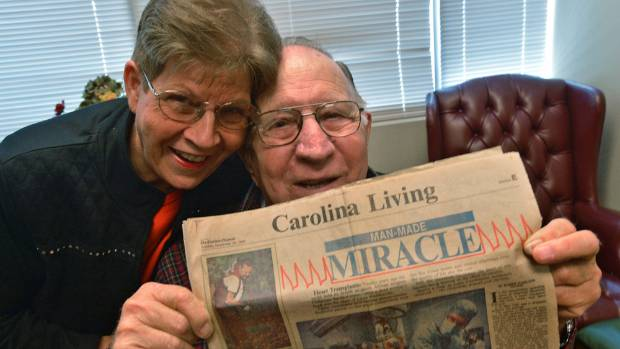 James and Louise Brock hold a copy of the Charlotte Observer from November 29, 1987, showing a photo of his heart ...