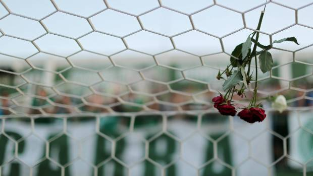 Flowers hang from a net, as fans mourn the devastating losses from the plane crash.