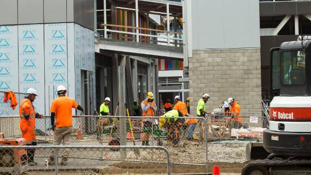 Workers lay pavers alongside the new complex.