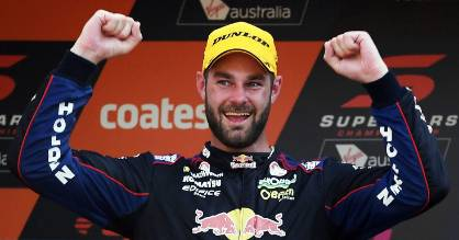 Shane Van Gisbergen reacts on the podium after finishing in 3rd place and winning the Supercars drivers Championship.