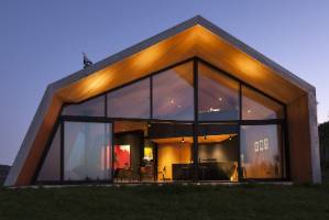 The steel-clad house has a distinctive architectural form. An entire wall of glazing maximises the extensive ocean views.