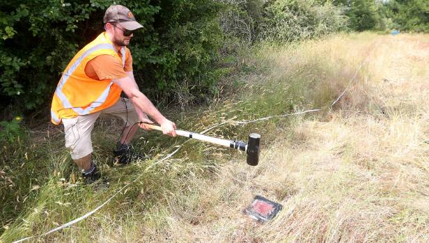 University of Auckland senior lecturer Dr Liam Wotherspoon sends vibrations into the soil beneath the stopbank at the ...