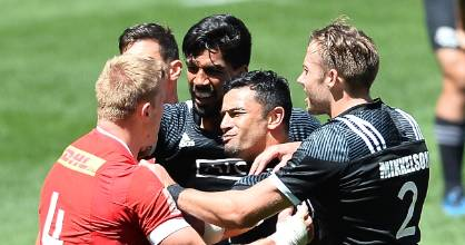 New Zealand players mix it up with Canada's John Moonlight during their Pool C match at the Cape Town Sevens.