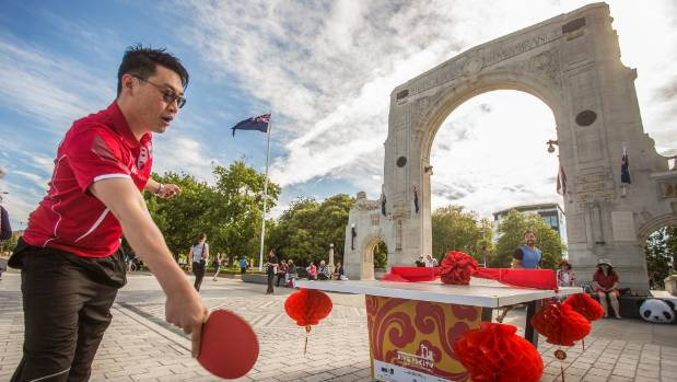 Ethan Lin battles Simon Fenwick, and a strong wind, at the opening of three table tennis tables near the Bridge of ...