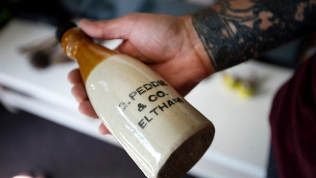 Vaughan Morresey shows off one of the items in his prized collection, a stone-made ginger beer bottle it took him five ...