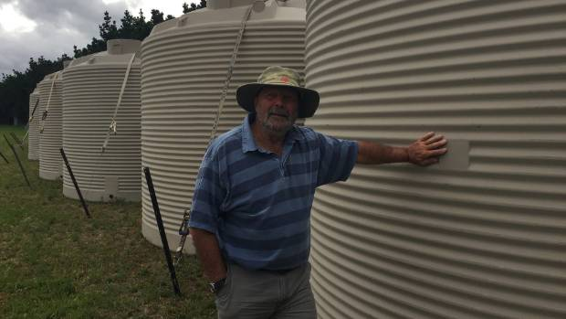 Ward Community Water Scheme chairman John Elliot beside the new water tanks installed this week.