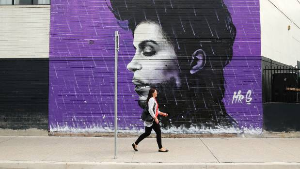 A woman walks past a Prince mural in Sydney, Australia.