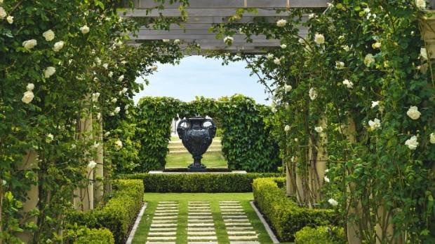 The view through the pergola ends with an urn and a mirror.
