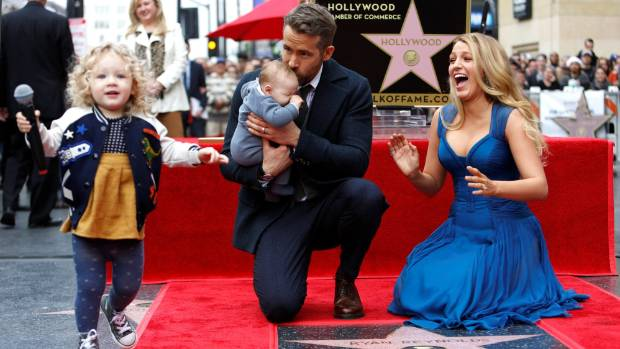Actor Ryan Reynolds kisses his daughter Ines while posing by his star with his actor wife Blake Lively and their ...