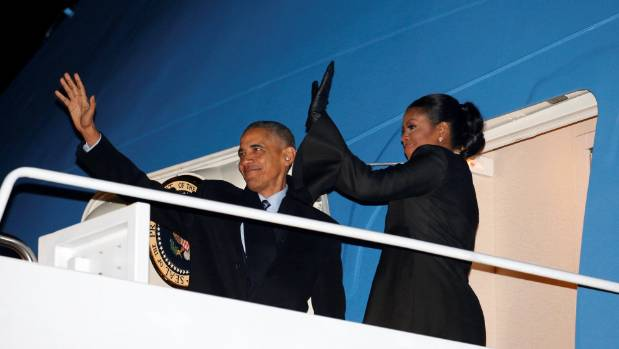 President Barack Obama and first lady Michelle Obama wave as they depart Joint Base Andrews in Maryland for Hawaii.