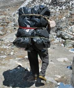 A porter carrying approximately 60 kgs heads towards Choala Pass in the Mt Everest region wearing plastic shoes.