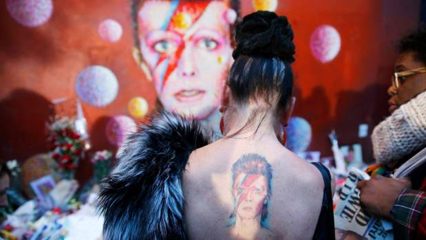 A woman with a Ziggy Stardust tattoo visits a mural of David Bowie in Brixton, south London, January 11, 2016.