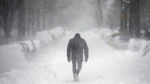 A man walks along a street covered by snow during a winter storm in Washington January 23, 2016.