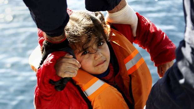 Greek Coast Guard officers move a girl from a dinghy carrying refugees and migrants aboard the Ayios Efstratios Coast ...