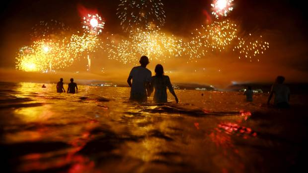 People watch as fireworks explode over Copacabana beach during New Year celebrations in Rio de Janeiro, Brazil, January ...