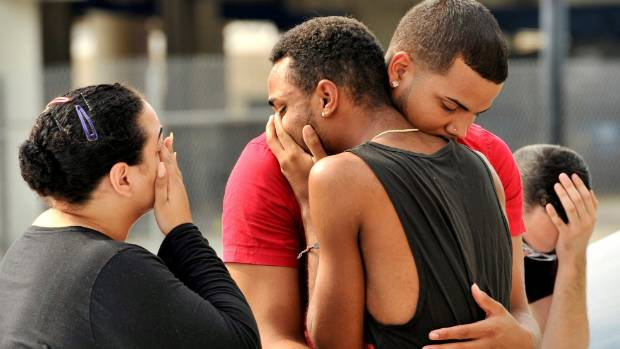Friends and family members embrace outside the Orlando Police Headquarters during the investigation of a shooting at the ...