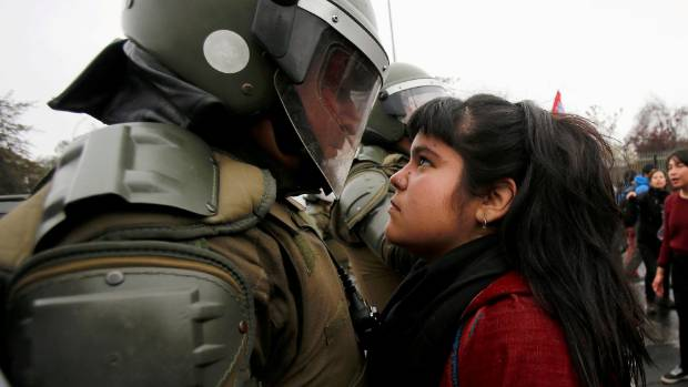 A demonstrator looks at a riot policeman during a protest marking the country's 1973 military coup in Santiago, Chile ...