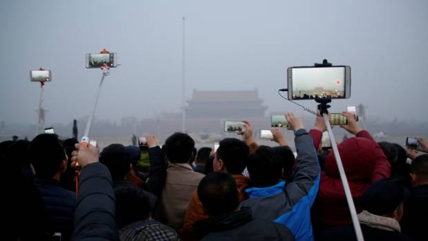 People take videos of a flag-raising ceremony during smog at Tiananmen Square.