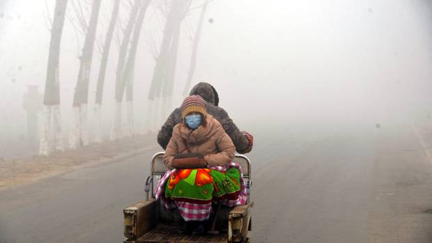 A woman sits on the back of a motorcycle in smog during a polluted day in Liaocheng, Shandong province.