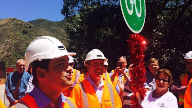 Transport Minister Simon Bridges turns a tinsel-wrapped Stop Go sign at the Kahutara Bridge to officially reopen SH1 ...