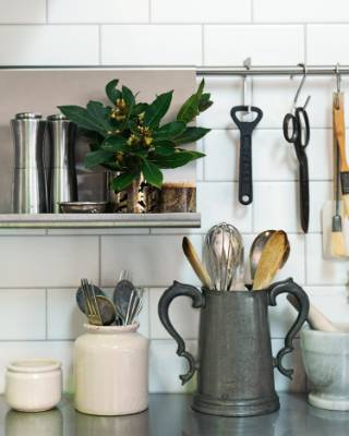 A stainless steel kitchen rail holds vintage pewter mugs and utensils; the renovated kitchen features stainless steel ...