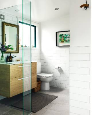 White tiles in the bathroom, which was the first room to be renovated; an old gilt mirror hangs above the vanity and the ...