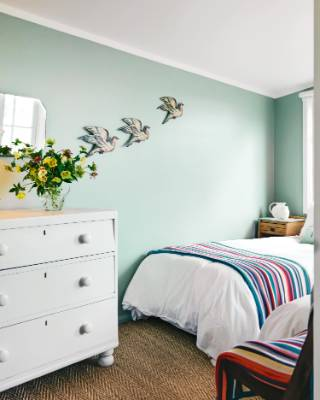 In the guest bedroom, the trio of hand-painted, cardboard birds adorning the wall originally came from a French toy.