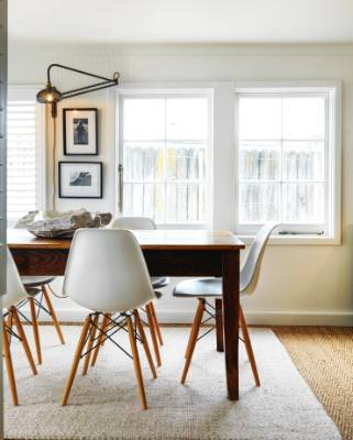 In the dining nook, adjacent to the front living area, a vintage French metal light fitting shines on a photograph of ...