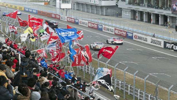 Members of the Nissan Supporters Association wave their flags as GT-R race cars flash down the Fuji Speedway straight.