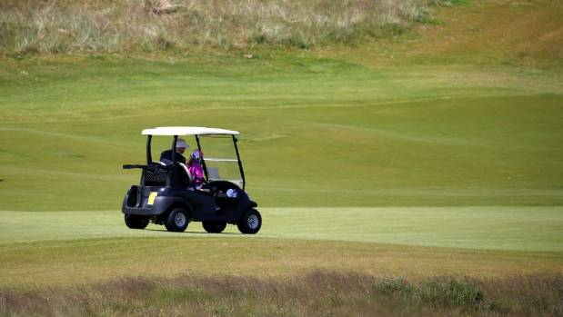 Trump drives a golf cart with his granddaughter Kai Trump at his Trump International Golf Links in Aberdeen, Scotland.